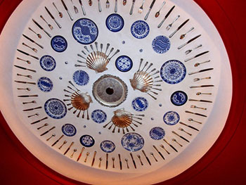 Blue and white plates on a red ceiling