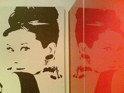 Audrey Hepburn next to bright red glossy wall