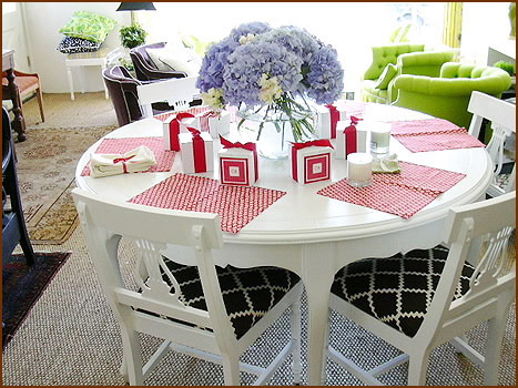 White dining table with four white and black chairs and pretty hydrangea in vase