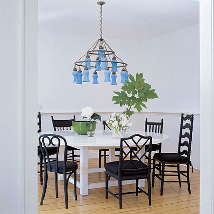 Sarah Jessica Parker's dining room with white table and different dining chairs painted black and gorgeous pale blue chandelier