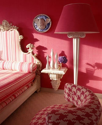 Plank on corbel as bedside table in a deep pink bedroom
