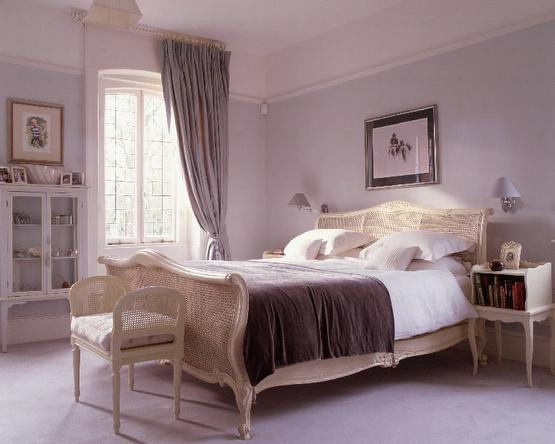 Bedside table with space for books in a mauve bedroom