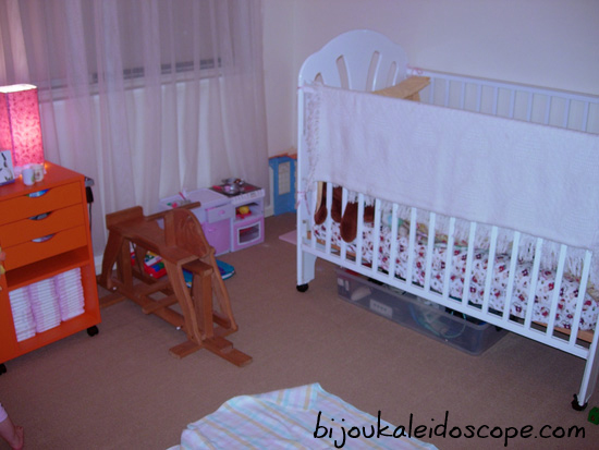 Hannah's room with white cot, vintage rocking chair and toy kitchen corner