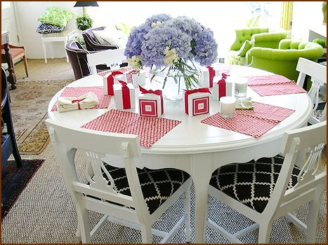 white round dining table with black and white chairs with red placemats