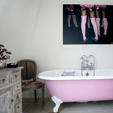 Pink clawfoot bath with art print with pink stockinged feet