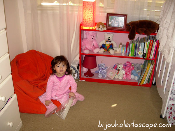 Hannah on her beanbag next to her pink and red bookcase