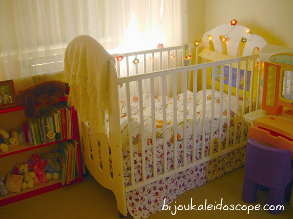 Hannah's cot next to her red and pink bookcase