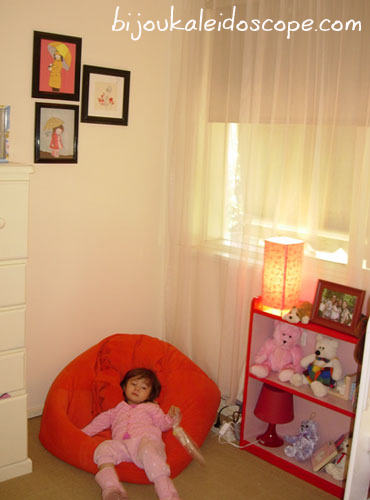 Hannah with her pink and red bookcase with her beanbag and small collection of artwork with girls with umbrellas