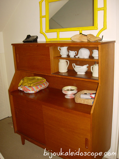Mid century hall cabinet with a few things in