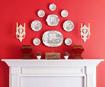Plates arranged above a mantlepiece in a red room