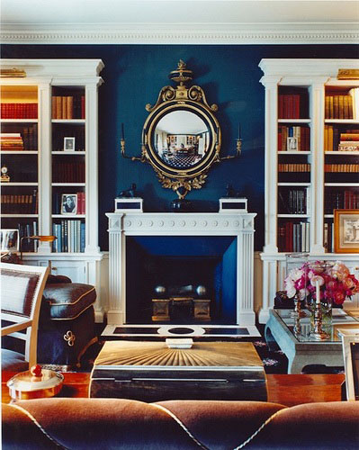 Antique crest-like gilt mirror in a deep blue library and living room