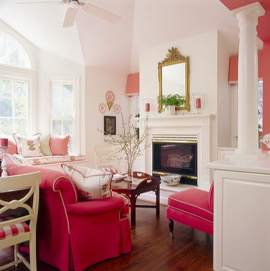Gilt ornate mirror above a fireplace in a while room with deep pink accents, via Kelley Proxmire