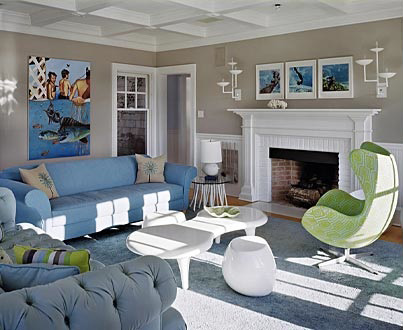 Triptypch paintings in a beige and white living room with blue furniture