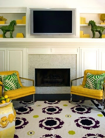 Flat screen TV above a fireplace in white living room with yellow and green accents