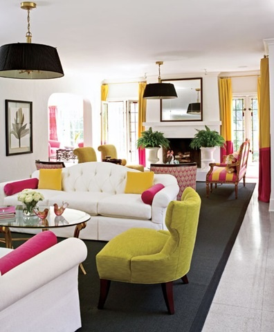 Bright furnishings enliven things up while black rug ground this white living room