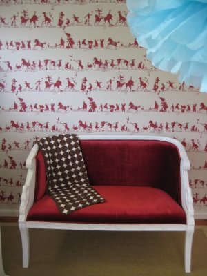 Red settee in nursery with red and white wallpaper, via ish and chi