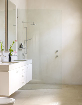 Cream tiled bathroom with glassed wall divider, via Clare Cousins Architects.