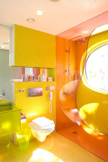 Glass divider between shower and rest of bathroom in a funky orange tint, via Karim Rashid.