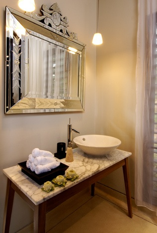 Large venetian mirror in a beautiful bathroom with a marble sink