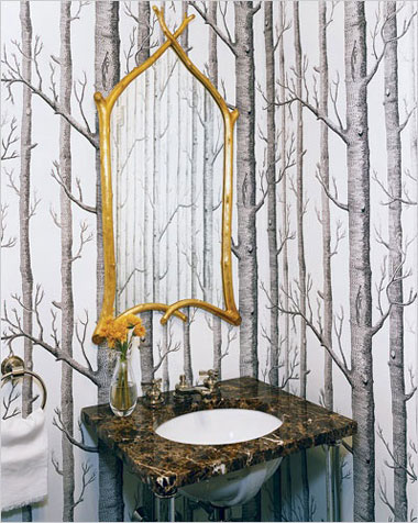 A gilt mirror with frame like branches in a forest wallpapered bathroom, via Philippe Starck.