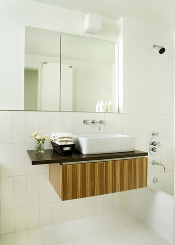 Floating vanity and sink cabinet in an all white bathroom