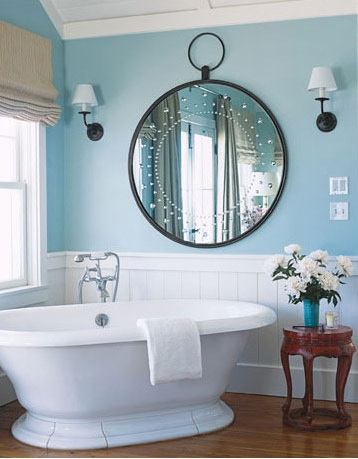Large white bathtub in a blue and white bathroom with super large round mirror