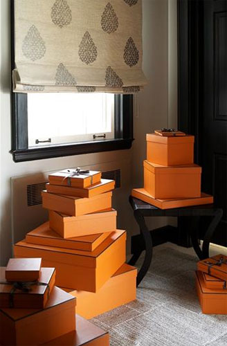 Orange Hermes boxes in orange and white bedroom designed by Sara Story Designs
