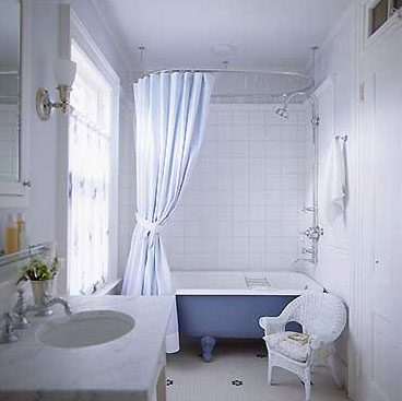 A simple white  bathroom with blue clawfoot bath, via Sherrill Canet Interiors