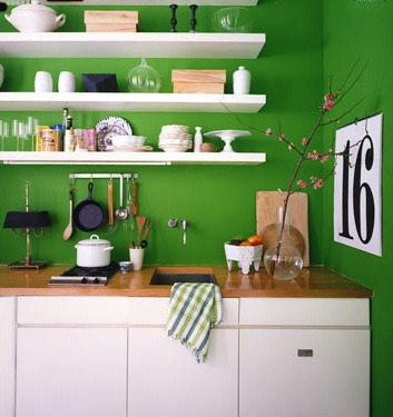 Verdant green kitchen with white shelving and cabinets, via Domino.
