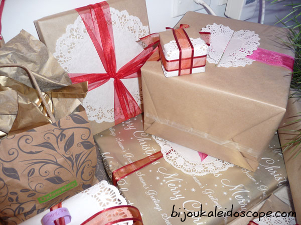 Simply wrapped gifts in browns, doiley tags and red ribbons