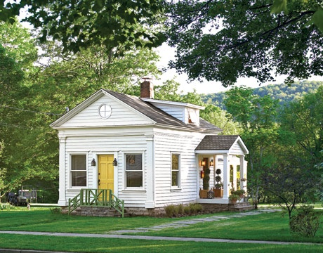 Yellow door in white house of the oft-featured  Monkey Cottage, via Country Living