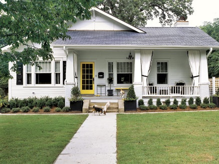 Sweetest white house with yellow door and black accents, via Country Living