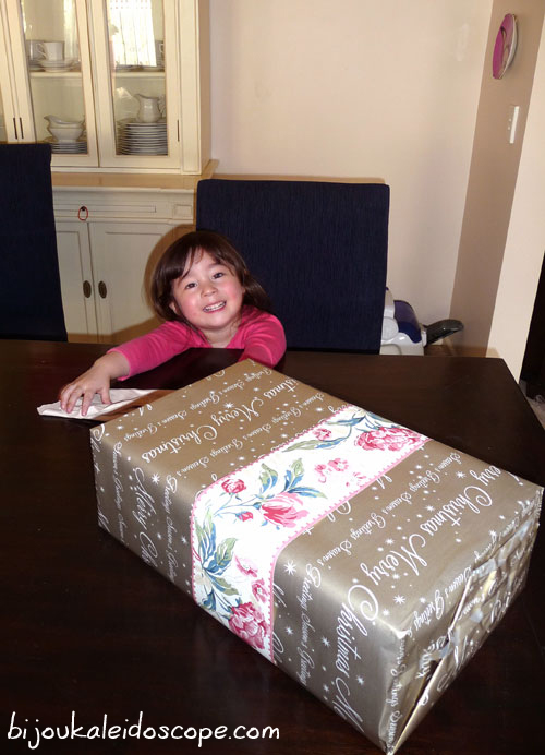 Hannah with glee over her wrapped Birthday Present using my wallpaper border as accent.