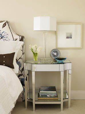 Mirrored side table with a few small items.