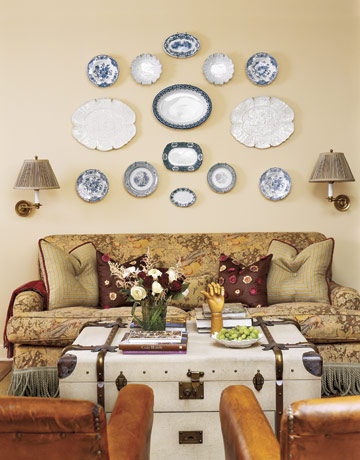 Wall of white and blue plates with vintage trunk as coffee table, via Country Living
