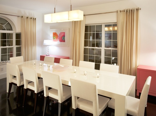 Simple white dining table with pink accents and white chairs
