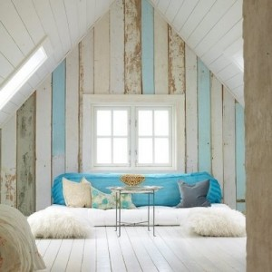 Loft with pitched roof and pale blue woodwork panels lining the walls