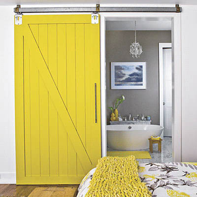 Large yellow barn door into a bathroom, via Southern Living