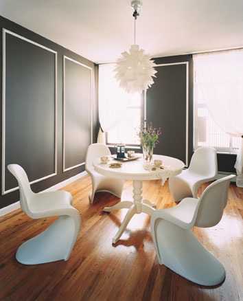White Panton chairs in a dining space with black walls and wooden floorboards, via Domino Mag