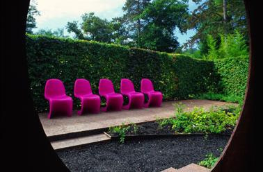 Hot pink Panton chairs in a garden