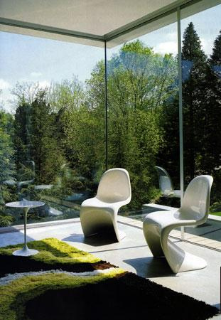 The white Panton chairs create architecture, texture and lines against the all-glassed room