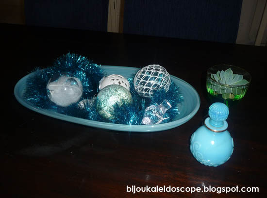 The blue Italian glassware with some blue tinsel and blue baubles on the table