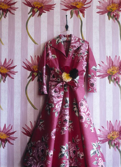 Deep pink dress hung on pink and red wallpapered wall, via Sarah Kaye