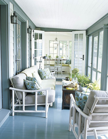 Porch painted with gloss blue and white cane furniture
