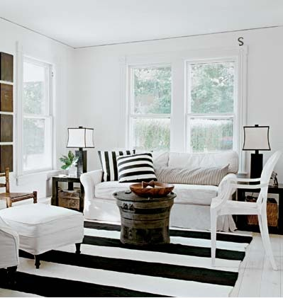 Black and white striped rug in an all white living room, via Cottage Home