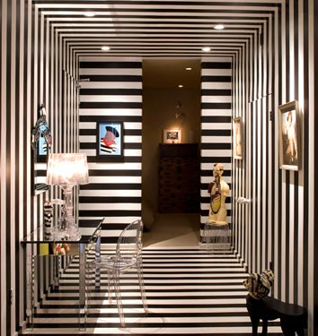 A completely black and white striped wallpapered (including ceiling)  foyer and hallway, via Domino