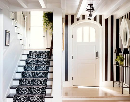 Black and white striped foyer contrasted with black and white tiger print stair rug, via House Beautiful