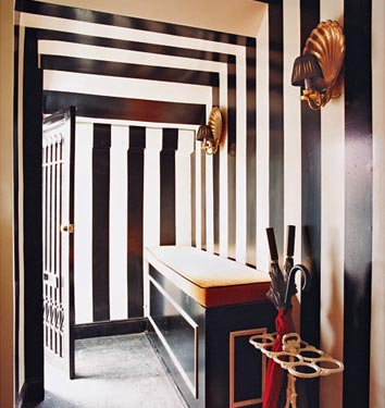 A black and white striped hallway leading to bright rooms, via Domino Mag