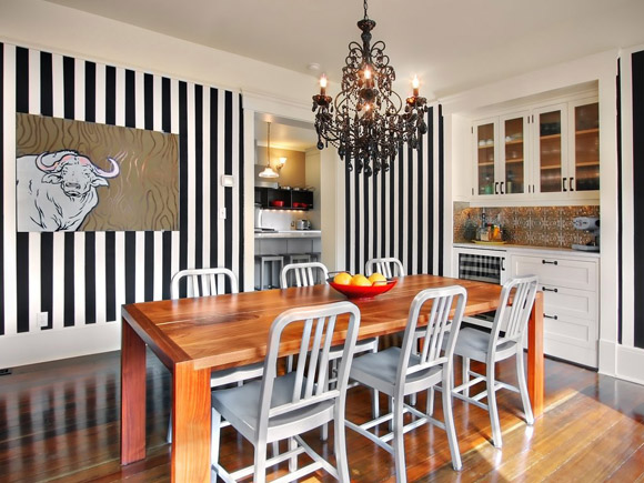 Black and white stripes adorn the wall of this dining room