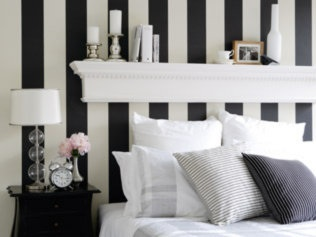 BLack and white stripes behind bed creates a large presence bedhead, via COuntry Living